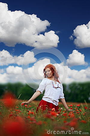 Redheaded woman in poppy field