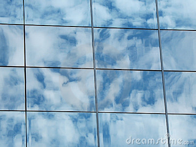 The reflection of the cloudy sky in the glass wall