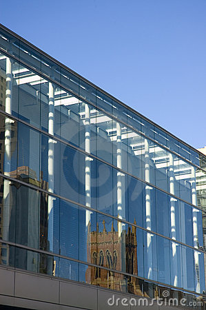 Reflection of old church on modern glass building