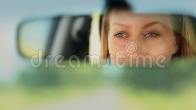 Reflection of woman's blue eyes in rearview mirror stock video