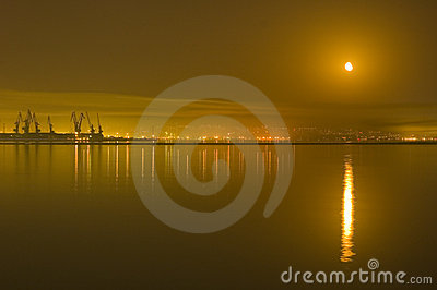 Reflections of city and moon in the Caspian Sea
