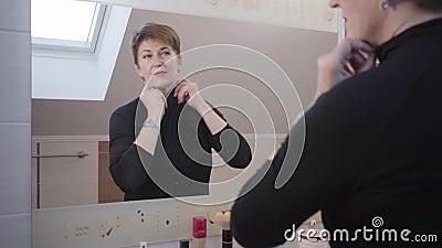 Reflexão de feliz madura caucasiana ajustando sua elegante roupa e cabelo em frente ao grande espelho Cheio sênior video estoque