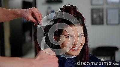 Reflexão do cabeleireiro que faz o corte de cabelo para a mulher no salão de beleza do cabeleireiro Conceito da forma e da beleza filme
