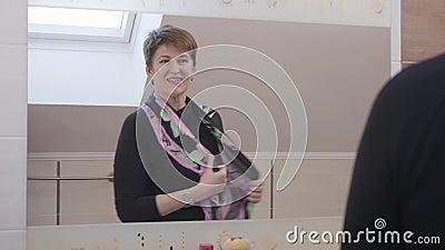 Reflexão estreita de uma mulher madura positiva que coloca o cachecol colorido em frente ao grande espelho e sai Elegante filme