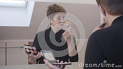 Reflexão estreita no espelho de uma mulher caucasiana sênior olhando para o grande espelho e aplicando pó facial Linda madura video estoque