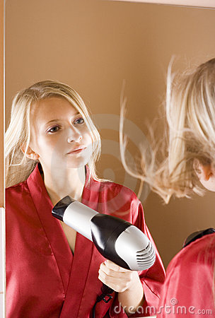 Reflexion of young blone woman using hair drier
