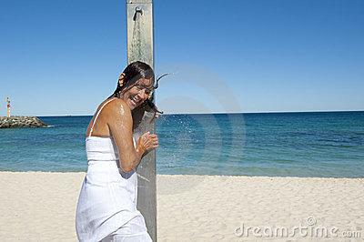 Refreshing shower for sexy woman at the ocean