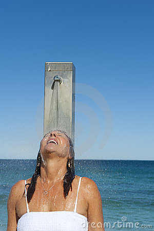 Refreshing shower for woman at the ocean