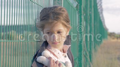 Refugee homeless child. portrait of Caucasian little girl standing in front of metal fence, she is unhappy and resentful. Refugee homeless child. portrait of stock video footage