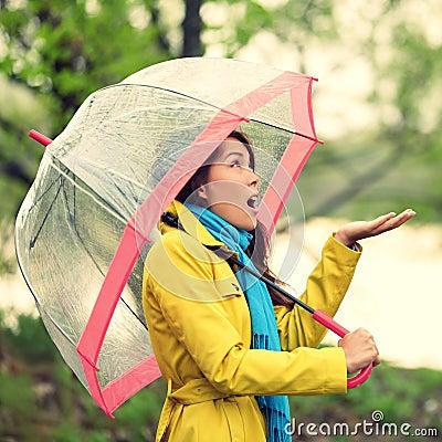 Regenschirmfrau im Herbst aufgeregt unter Regen