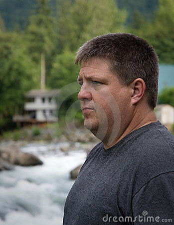Regular guy meditating and thinking near the river