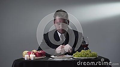 Reicher Geschäftsmann in einer Klage, die ein Stück Fleisch nahe bei Äpfeln, Trauben und einem Glas Rotwein eatting oder geschmec stock video