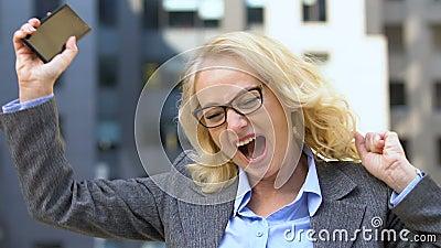 Reife weibliche Büroangestellte freuen sich über gute Nachrichten vom Telefon über Gehaltserhöhung stock video footage