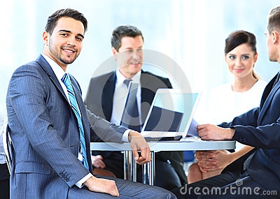 Reifer Geschäftsmann, der während der Sitzung mit Kollegen lächelt