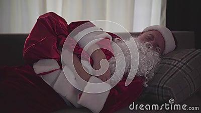 Reiziger Caufcasianer in Santa Claus Kostüm schlafen auf einem Sofa mit Geschenken Erschöpfter alter Kerl stock video footage
