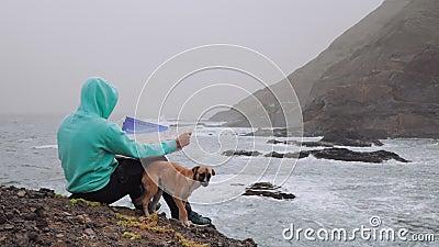 Reiziger met een hondenkaart voor krachtige golven die in een rotsachtige kustlijn springen Enorme vulkanische bergen ruw stock videobeelden