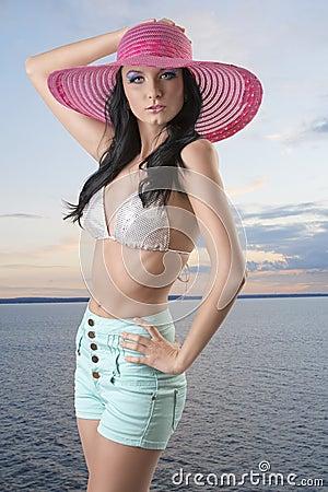 Reizvoller Brunette mit Kurzschlüssen, Hut und der Hand auf der Hüfte