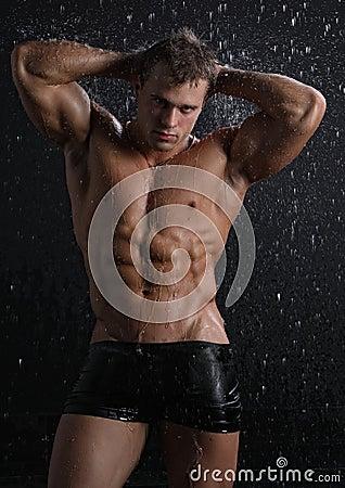Reizvoller junger Mann des nassen Muskels, der unter dem Regen aufwirft