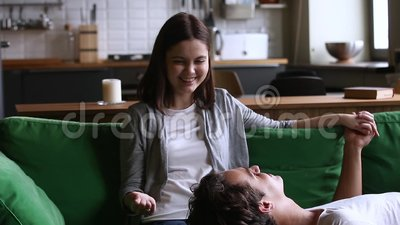 Relajación que habla de los pares adolescentes cariñosos jovenes en el sofá junto almacen de metraje de vídeo