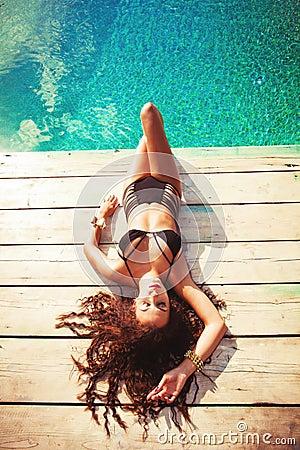 Relaksuje przy basenem