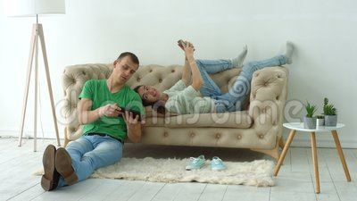 Couple using digital devices on cozy couch at home stock video