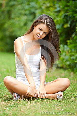 Relaxed beautiful brunette sitting on grass