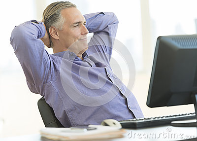 Relaxed Businessman Sitting With Hands Behind Head At Desk