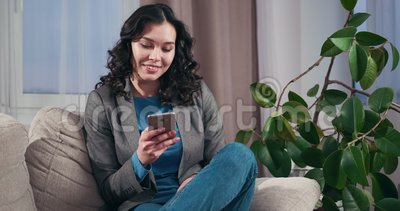 Relaxed businesswoman text messaging on mobile phone. Relaxed businesswoman sitting on sofa and text messaging on mobile phone stock footage