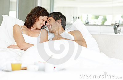 Relaxed couple lying on bed with breakfast