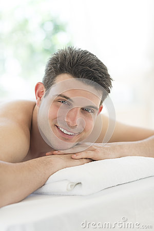 Relaxed Man Lying On Massage Table At Spa