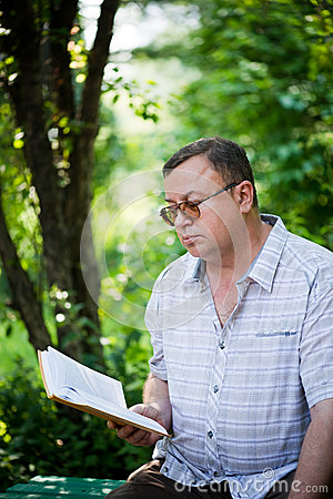Relaxed man sitting in park and reading