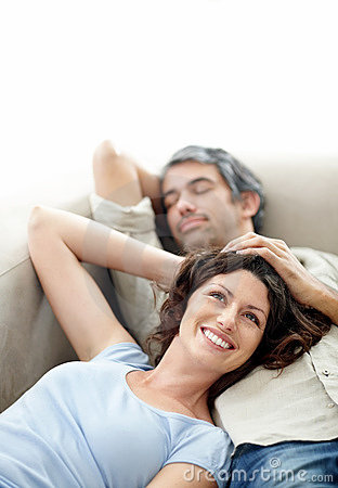 Relaxed mature couple on couch with copyspace