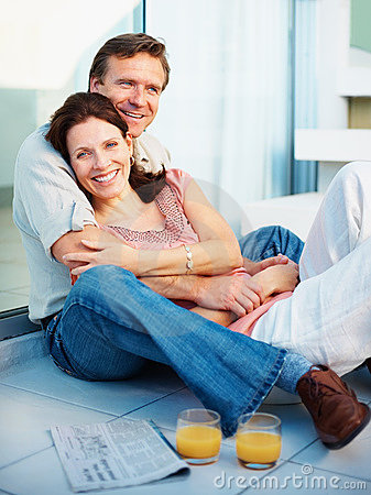 Relaxed mature couple sitting with juice glasses