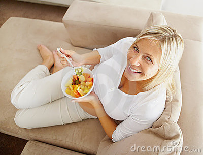 Relaxed mature woman on couch eating fruit salad
