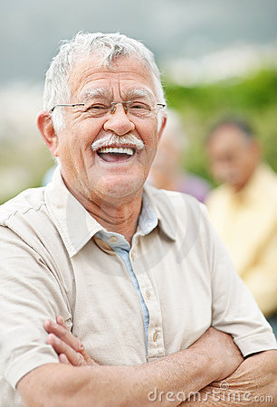 Relaxed old man laughing outdoors