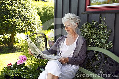 Relaxed old woman reading newspaper