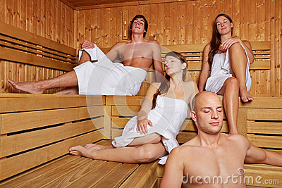 Relaxed people sitting in sauna