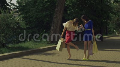 Relaxed pretty women walking on street after shopping stock video