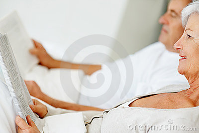 Relaxed senior couple lying and reading a magazine