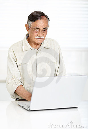 Relaxed senior man working on a laptop