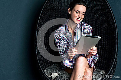 Relaxed sensual woman operating touch pad