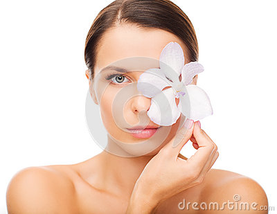 Relaxed woman with orсhid flower over eye