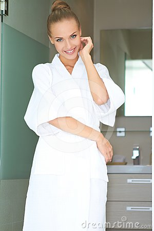 Relaxed woman standing in white bathrobe