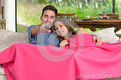 Relaxed young couple watching tv at home in bright