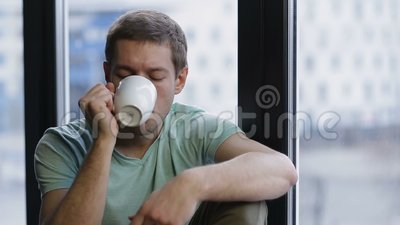Relaxed young hipster drinking coffee near window stock footage