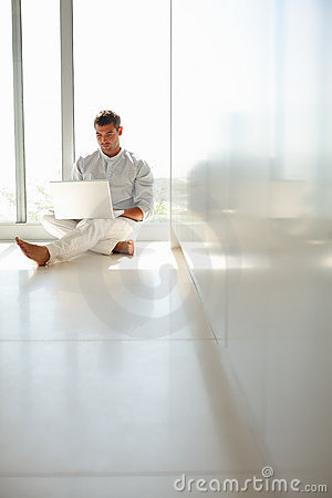Relaxed young man surfing on his laptop