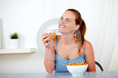 Relaxed young woman eating healthy breakfast