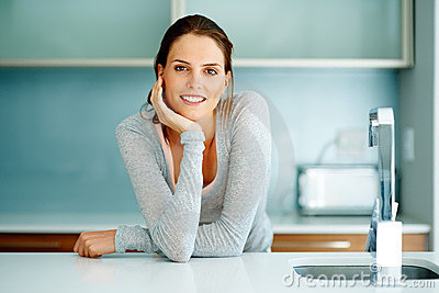 Relaxed young woman standing at the kitchen