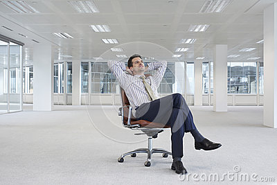 Relaxing Businessman On Chair In New Office