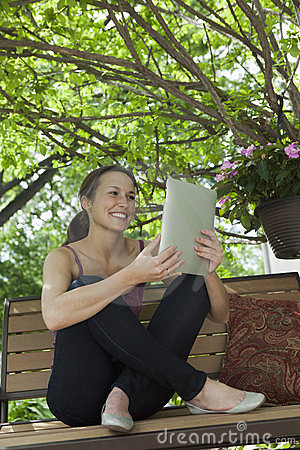 Relaxing outside reading a digital tablet